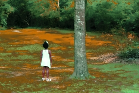 black girl in a white dress standing in a field next to a treet