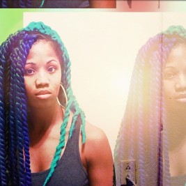Black woman with blue and green Senegalese twists