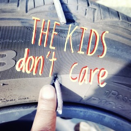 tire punctured by a steel rod with words the kids don't care