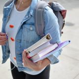student in jean jacket with a stack of books in hand and book sack on back