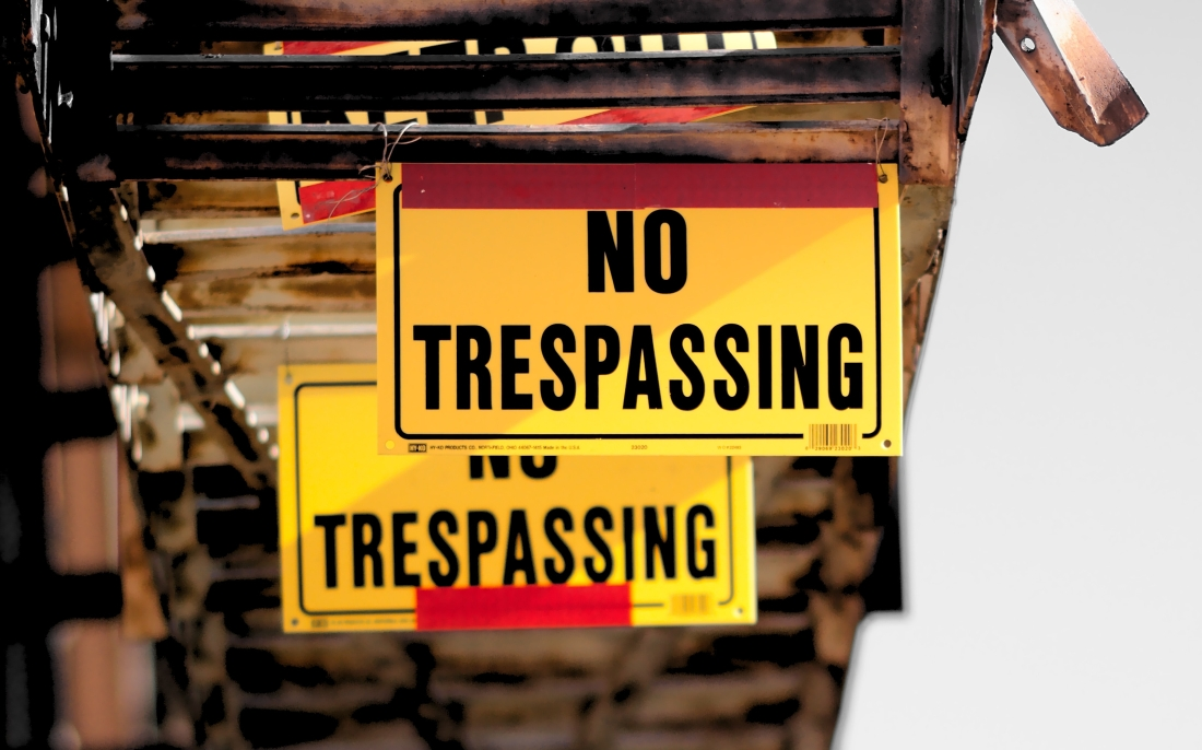 hanging signs that say no trespassing