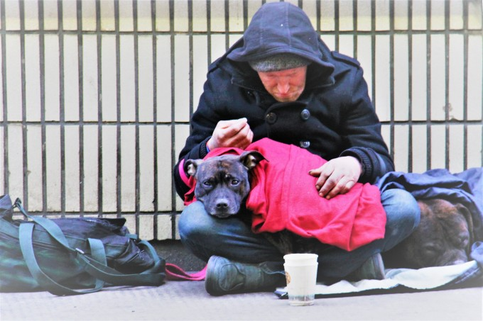 Sad man sitting on sidewalk with a dog in his lap and a paper cut on the ground in front of him