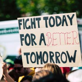 """cardboard protest sign reading """"fight today for a better tomorrow"""""""