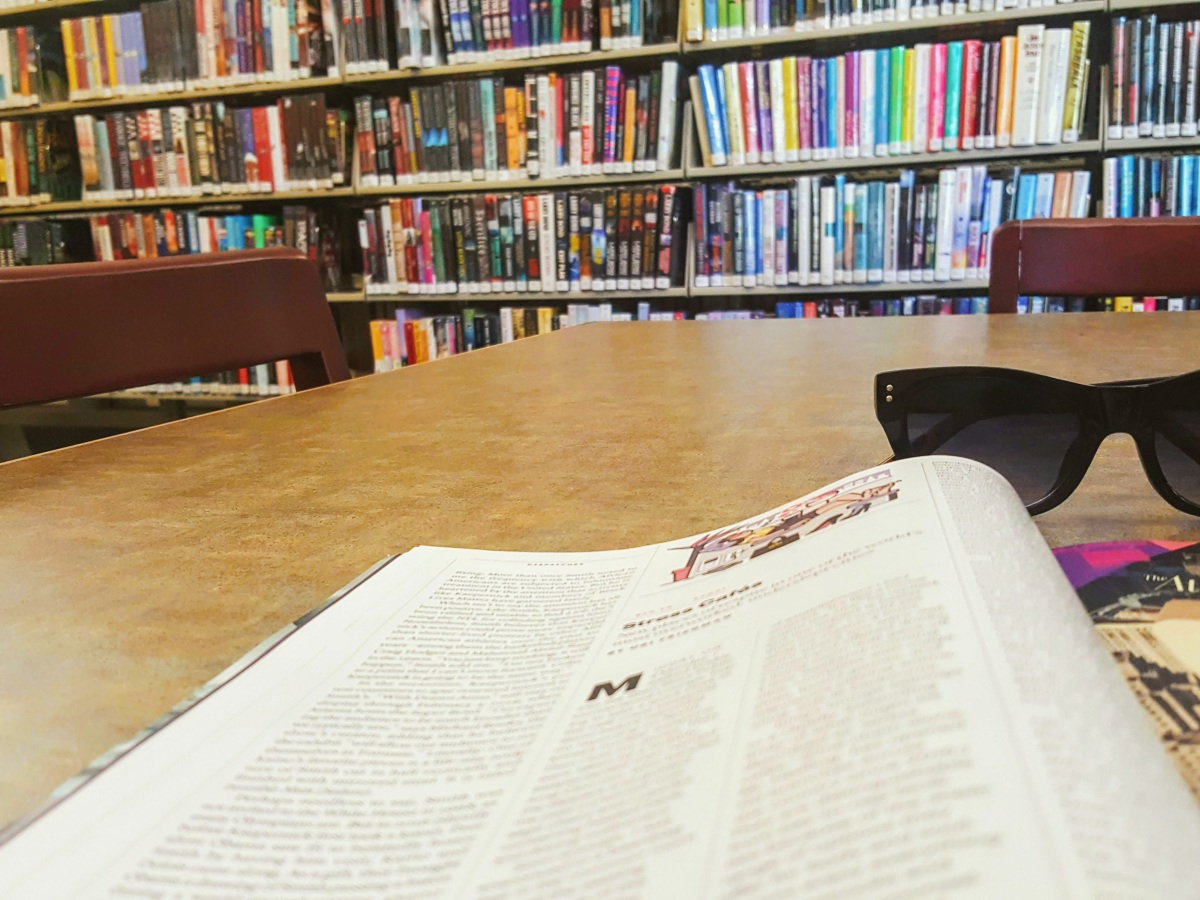 An open magazine and sunglasses sitting on a table with full library shelves in the background