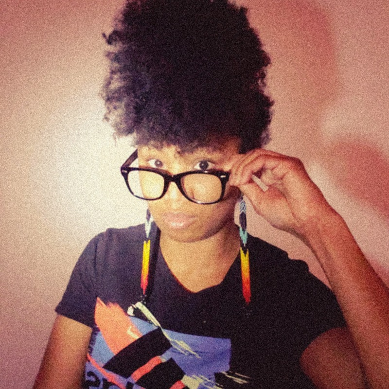 Joi wearing an afro mohawk, thick frame black glasses, and colorful bead earrings