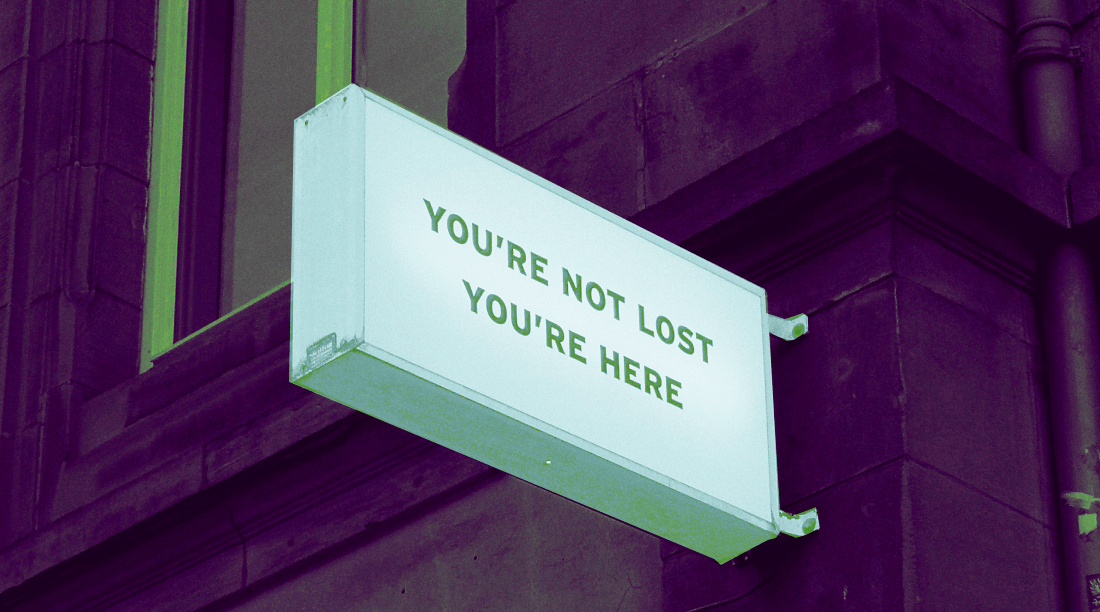 "sign on a building that says ""you're not lost. you're here"""