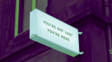 """sign on a building that says """"you're not lost. you're here"""""""