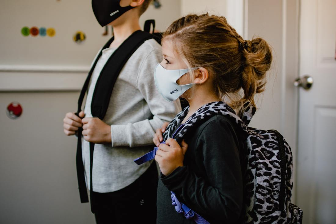 Two young students standing side by side wearing backpacks and face masks